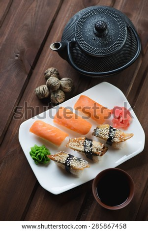 Sushi set on a white glass dish with soy sauce and tea, top view, selective focus - stock photo