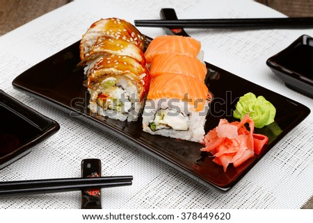 Sushi set on plate with wasabi and marinated ginger on wooden table with soy sauce
