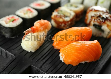 Sushi set on wooden board, close up
