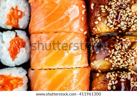 Sushi Set sashimi and sushi rolls served on dark plate. Image of Japanese food on dark background. Top view. - stock photo