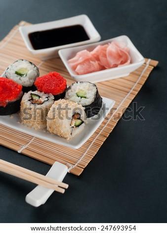 Sushi set served on black background, selective focus - stock photo