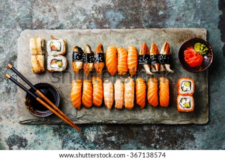 Sushi Set served on gray stone slate on metal background - stock photo