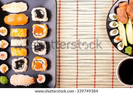 Sushi set, soy cheese, lime, avocado,  red caviar, black caviar,  soy sauce, wasabi on black background - stock photo