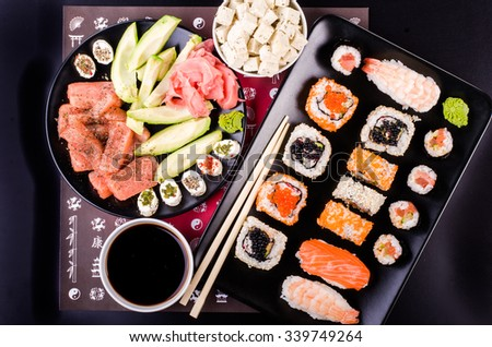 Sushi set, soy sauce, ginger, wasabi, black and red roe, avocado, salmon, cheese on black background  - stock photo
