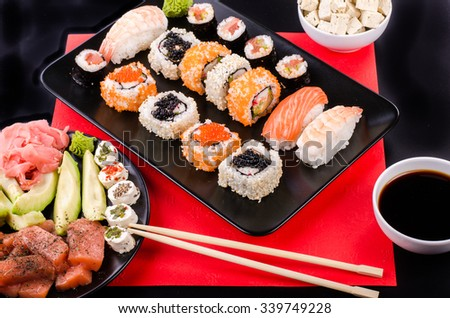 Sushi set, soy sauce, ginger, wasabi, black and red roe, avocado, salmon, cheese on black and red background.  - stock photo
