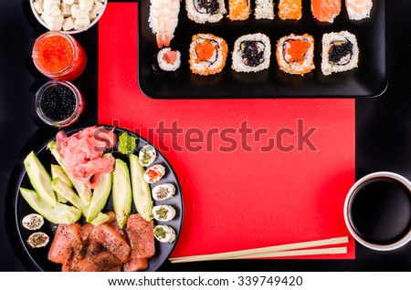 Sushi set, soy sauce, ginger, wasabi, black and red roe, avocado, salmon, cheese on black and red background. Free space for your text - stock photo