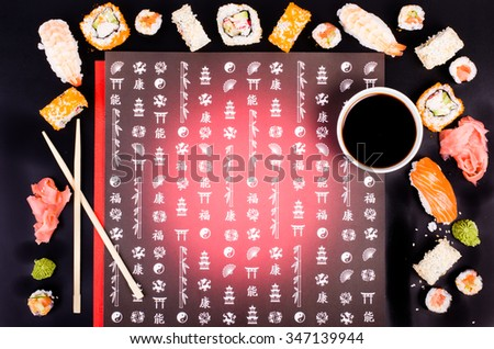 Sushi set, soy sauce, wasabi on black background with Japanese characters - stock photo