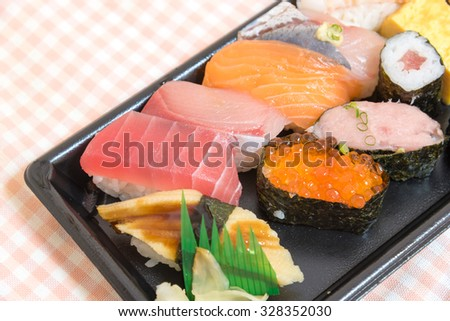 Sushi set: sushi roll with salmon and sushi roll with smoked eel. Sushi Set sashimi and sushi rolls served on stone slate. Sushi rolls with salmon and hot tea ceremony on white wooden table.