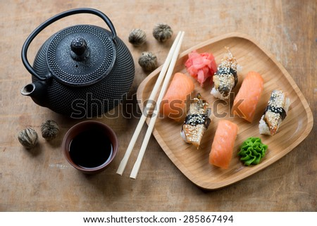 Sushi set with a soy sauce, chopsticks and tetsubin teapot, selective focus - stock photo