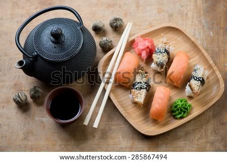 Sushi set with a soy sauce, chopsticks and tetsubin teapot, selective focus - stock photo