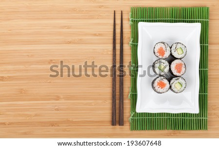 Sushi set with salmon and cucumber over bamboo table with copy space - stock photo