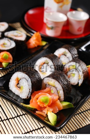 sushi set with salmon,avocado and cucumber on black plates