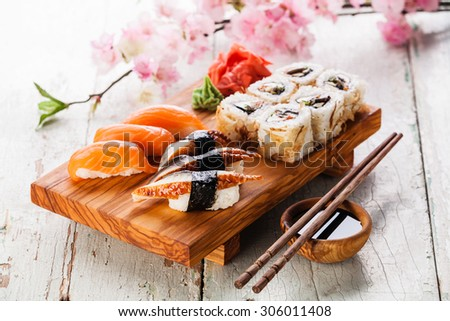 Sushi Set with sashimi and sushi rolls on olive wood board on blue wooden background - stock photo