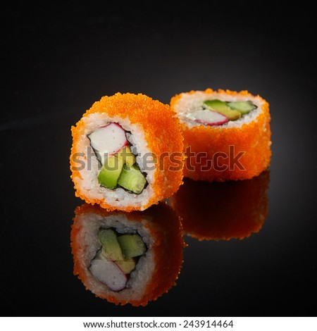 sushi with cucumber and crab sticks on black background - stock photo