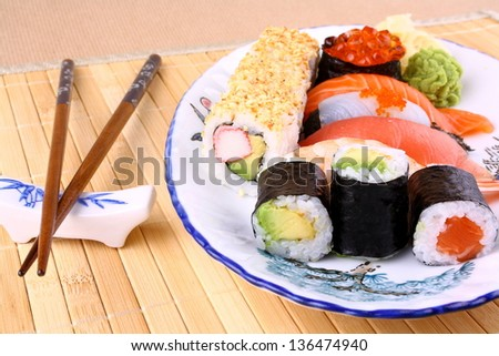 Sushi with red caviar and chopsticks, close up