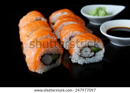 sushi with salmon and avocado on black background