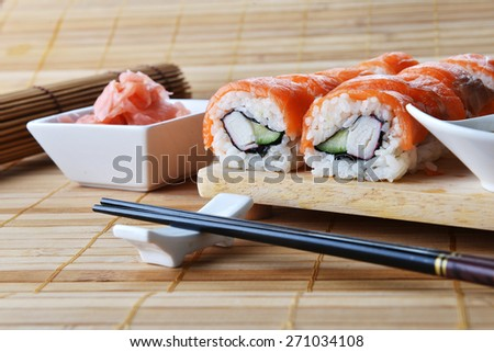 sushi with salmon and avocado on wooden background - stock photo