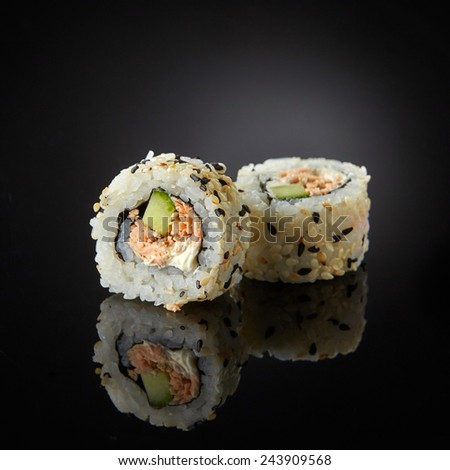 sushi with salmon and cucumber on black background - stock photo