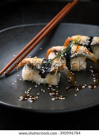 Sushi with smoked eel. Unagi nigiri and chuka salad with sauce and sesame seeds on a dark background. - stock photo