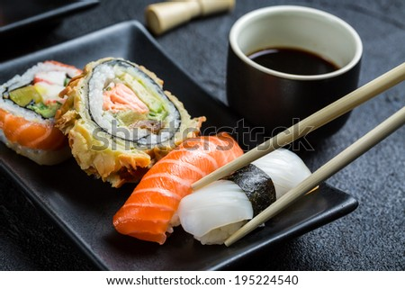 Sushi with soy sauce eaten with chopsticks