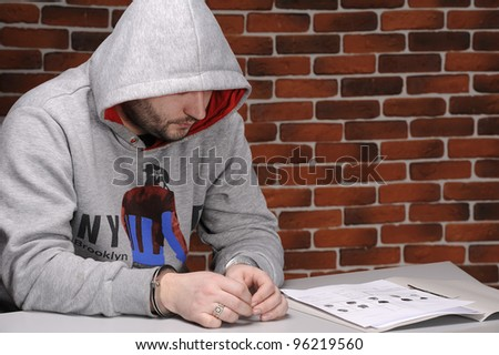 Suspect in handcuffs sitting at table against a break wall - stock photo