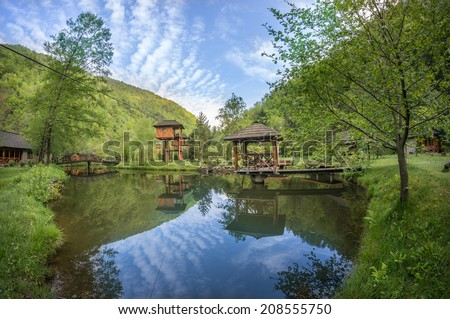 suspended cottage near pond with small pontoon
