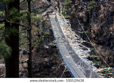 Suspension bridge across the river on the way to Namche Bazar - Nepal, Himalayas - stock photo
