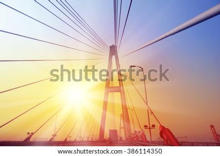 Suspension bridge against sunset sky. - stock photo