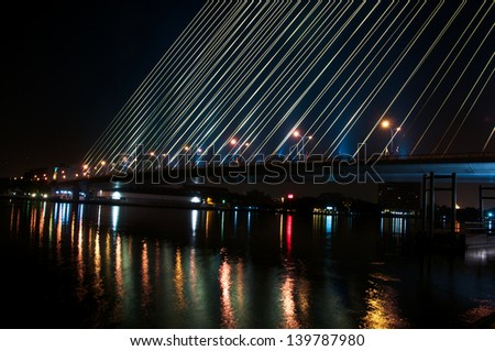 Suspension bridge at night in bangkok,Thailand.The name is Rama 8. - stock photo