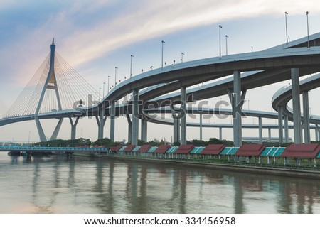 Suspension bridge connect to highway interchange river side with beautiful blue sky - stock photo