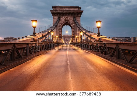 Suspension Bridge in Budapest, Hungary early morning. This image is toned. Focus on the road.