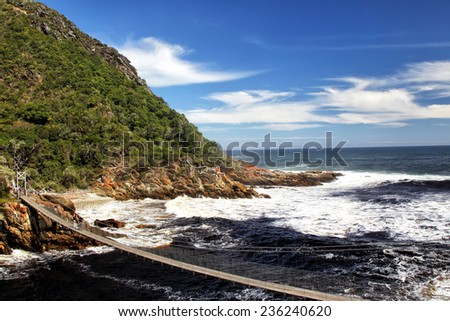Suspension bridge over the river mouth of the Storms River in the Tistsikamma National Park, South Africa. - stock photo