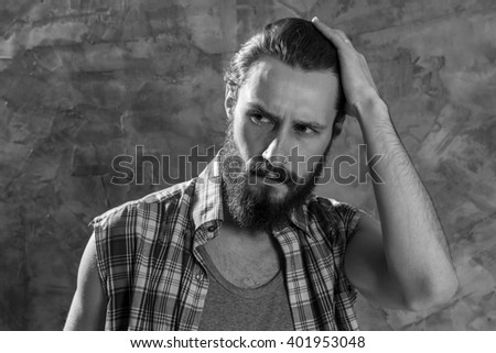 Suspicious look. Monochrome portrait of a bearded man looking away suspiciously.