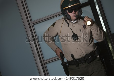 Suspicious middle aged policeman with flashlight drawing gun from belt against door - stock photo