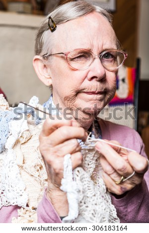 Suspicious old woman in pink sweater crocheting at home - stock photo