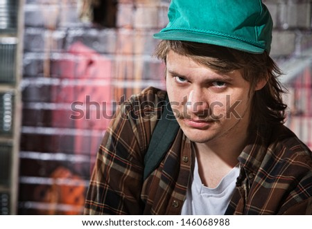Suspicious unemployed European male with hat - stock photo