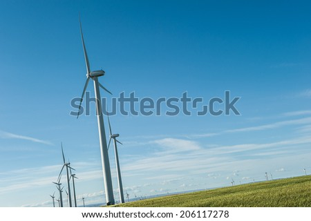 Sustainable wind energy generators against blue sky; renewable energy that helps fight against global warming