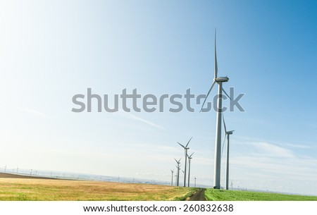 Sustainable wind energy generators against blue sky; renewable energy that helps fight against global warming - stock photo