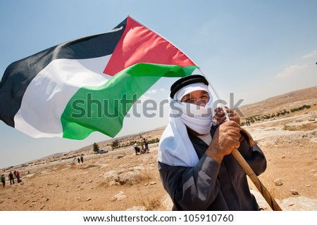 SUSYA, OCCUPIED PALESTINIAN TERRITORIES - JUNE 22: An elderly Palestinian man waves a flag in a demonstration near Susya, West Bank, on June 22, 2012. - stock photo