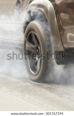 Suv car burns rubber off its tires in preparation for the race - stock photo