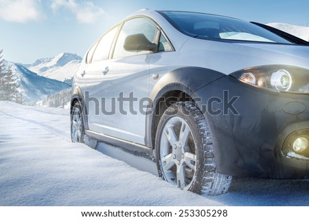 SUV car on snow covered mountain road - stock photo