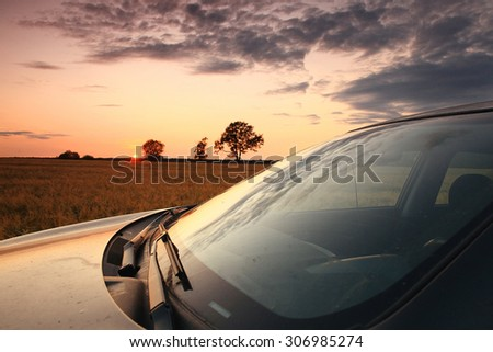 SUV in a wheat field sunset - stock photo
