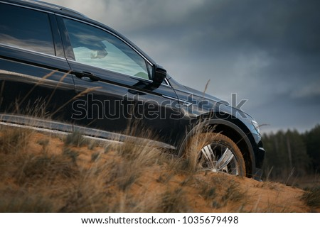 SUV on the hill of sand and grass