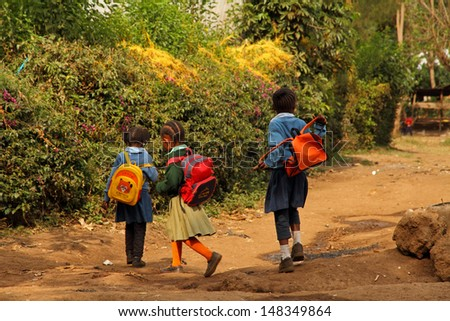 SUYE, TANZANIA - SEPTEMBER 10 : Three young African schoolgirls walk home from school in their uniforms in Suye, Tanzania on September 10, 2012.  Nearly all schools in Tanzania require uniforms. - stock photo