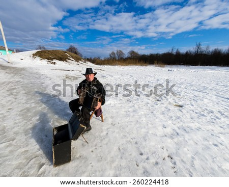 SUZDAL, RUSSIA - March 08, 2015: Winter day in the Russian city Suzdal. One of the most popular from Golden Ring cities. A man playing on accordion - stock photo