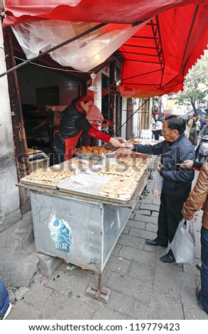 SUZHOU, CHINA - NOV 6: Shopper purchase roast sesame bun on November 6, 2012 in Shantangjie, Suzhou, China. Shantangjie is a 1100 year old historic market street build in 825 AD in the Tang Dynasty.