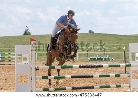 "SVEBOHOV, CZECH REPUBLIC - AUG 20: Front view of horseman in blue jumping on a brown horse  at ""HobbyJumping Event  2016"" on August 20, 2016  in Svebohov, Czech Republic."