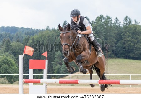 "SVEBOHOV, CZECH REPUBLIC - AUG 20: Young horseman in protective vest  during the jump on a brown horse at ""HobbyJumping Event  2016"" on August 20, 2016  in Svebohov, Czech Republic."