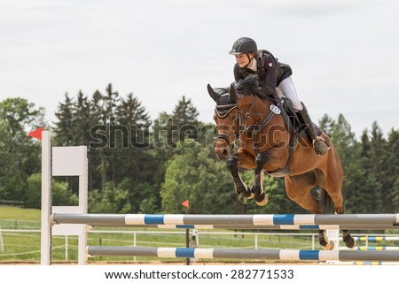 "SVEBOHOV, CZECH REPUBLIC - MAY 23: Happy young horsewoman is jumping over the hurdle at ""Summer Jumping Event  2015"" on May 23, 2015  in Svebohov, Czech Republic."