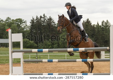 "SVEBOHOV, CZECH REPUBLIC - MAY 23: The young horsewoman is standing in the bracket at overcoming obstacles on horseback at ""Summer Jumping Event  2015"" on May 23, 2015  in Svebohov, Czech Republic."
